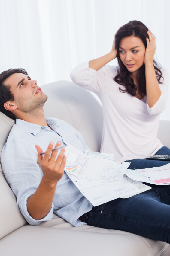 Couple looking stressed while doing their accounts sat on a couch