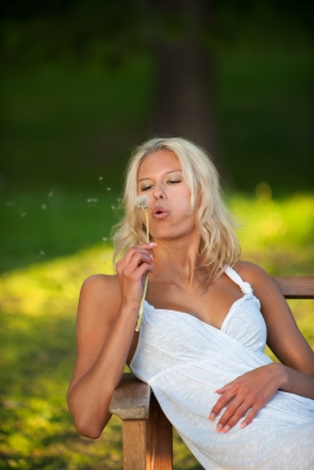a beautiful blond girl blowing seeds from a flower