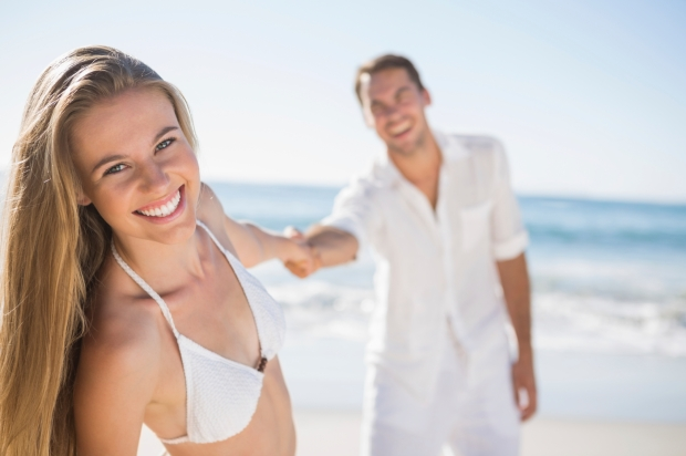Pretty woman smiling at camera with boyfriend holding her hand on the beach