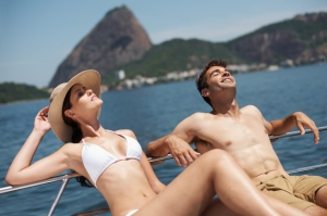 Shot of an attractive young couple relaxing on a yacht together