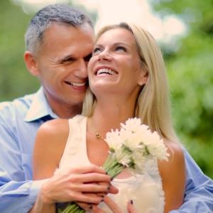 Shot of an affectionate couple enjoying the summer sun. Woman is holding flowers.