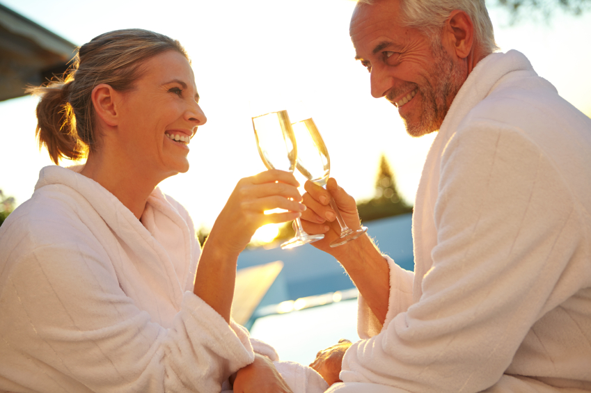 Shot of a mature couple drinking champagne while relaxing in deck chairs at sunset